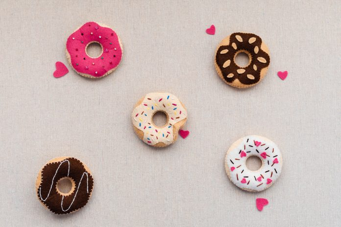 Flat lay of handmade felt doughnuts with colored chocolate are on a beige linen background. Concept romantic valentine's day gift, card mothers day. Card mothers day. Soft sweets for pretend food.