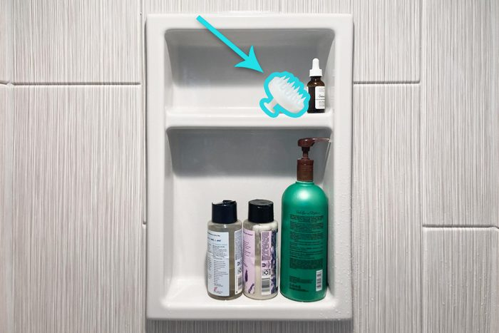 Scalp Brush on a shelf in a shower with other bottles
