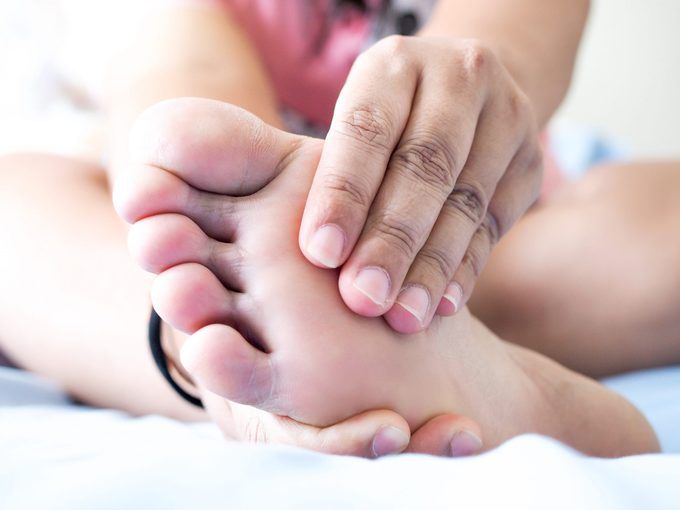 Asian woman sitting on bed Have foot pain Use hand massage to relieve pain And relax the foot muscles, Plantar Fasciitis disease.