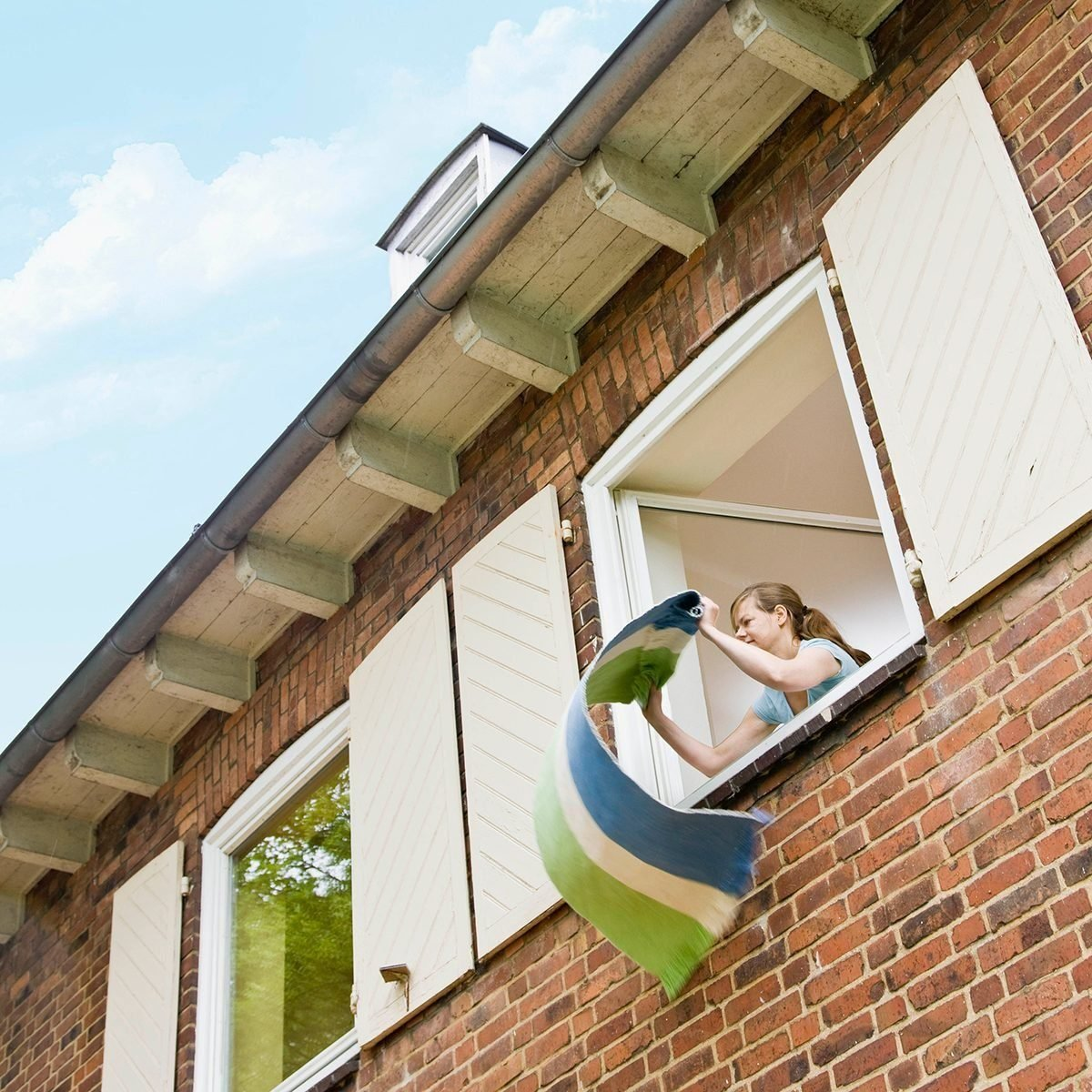 Woman Cleaning A Rug Out A Window