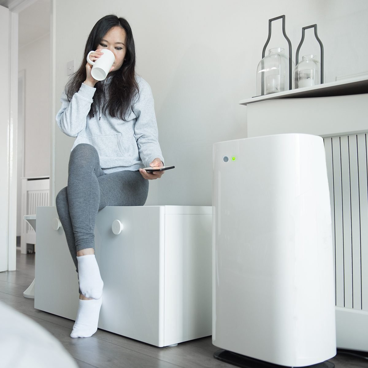 A Young Asian Woman Controls The Power Of Her Smart Air Unit From Her Mobile Phone As She Sits On A Storage Bench And Enjoys A Cup Of Tea In The Bedroom
