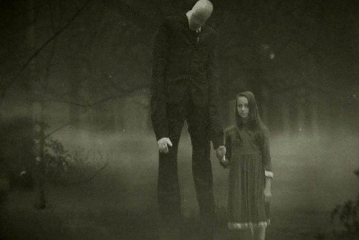 Little girl holding the hand of the slenderman