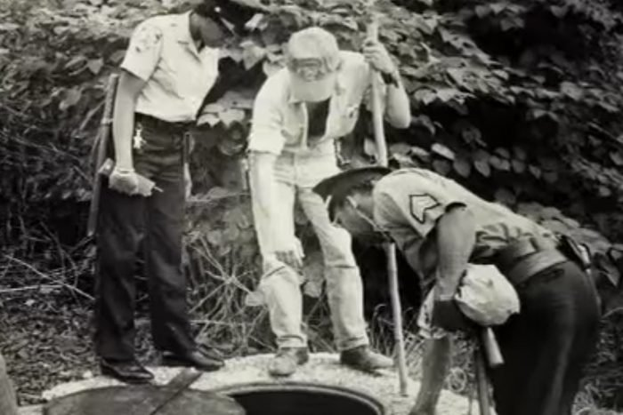 Black and white photo of officers investigating a hole