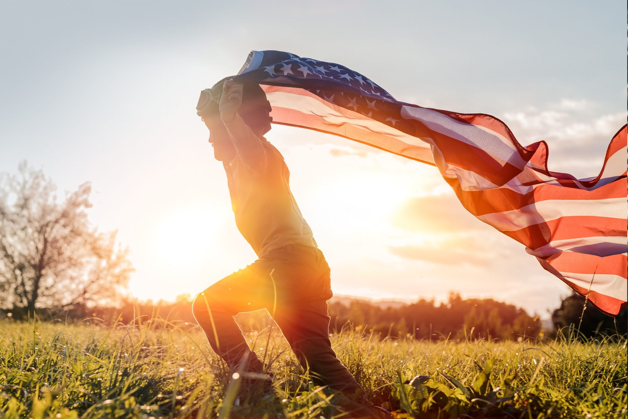 Little boy running with American flag at sunset