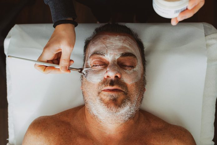 Cropped Hands Applying Cream On Man Face At Spa