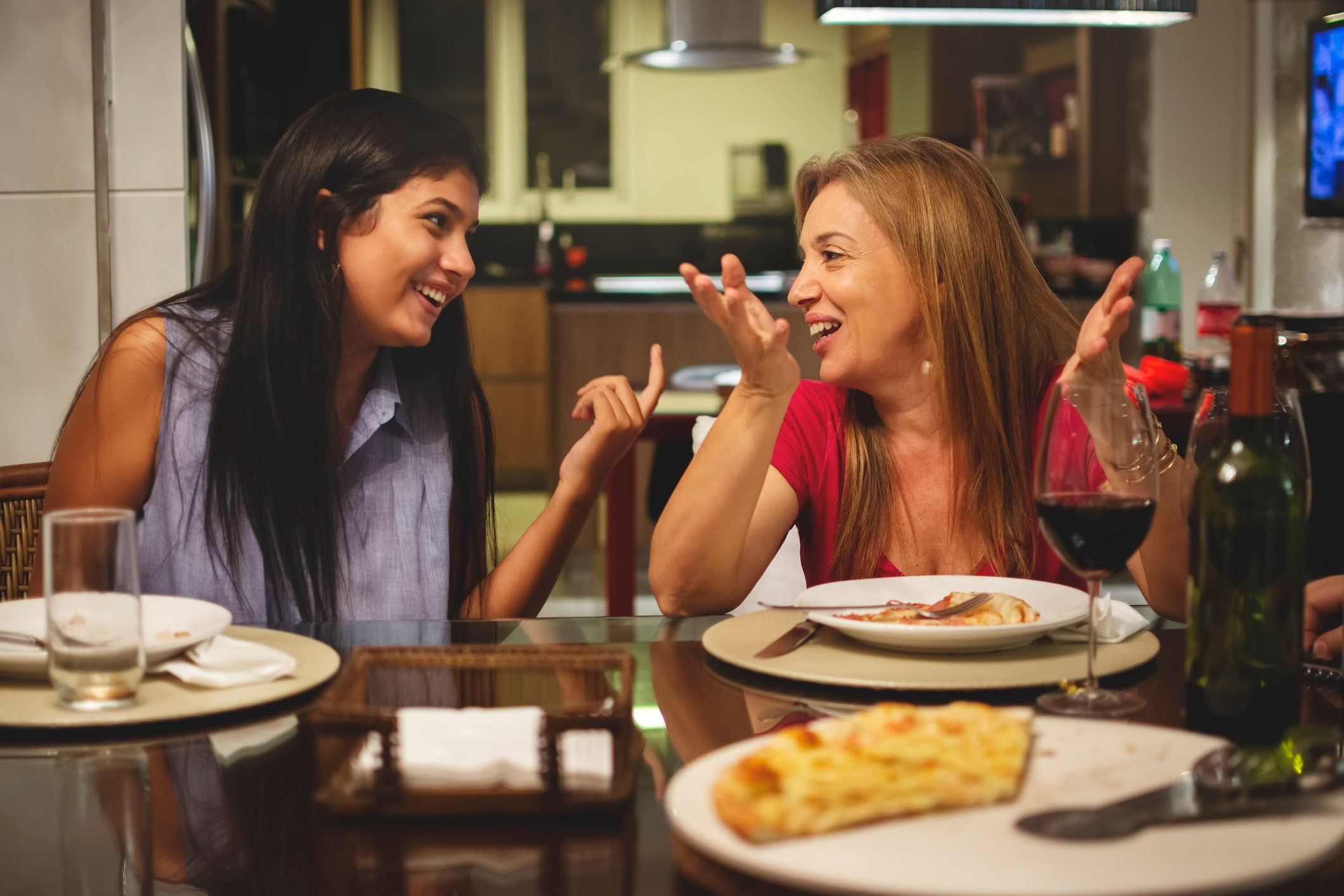 Mother and daughter eating pizza together at dining table and talking.