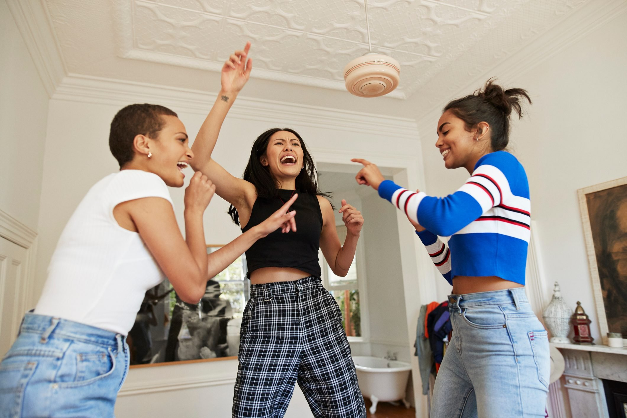 Young friends dancing and enjoying in bedroom
