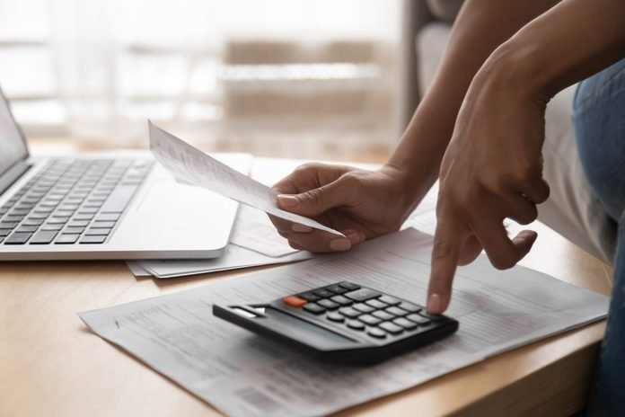 African woman holding paper bills using calculator, close up view