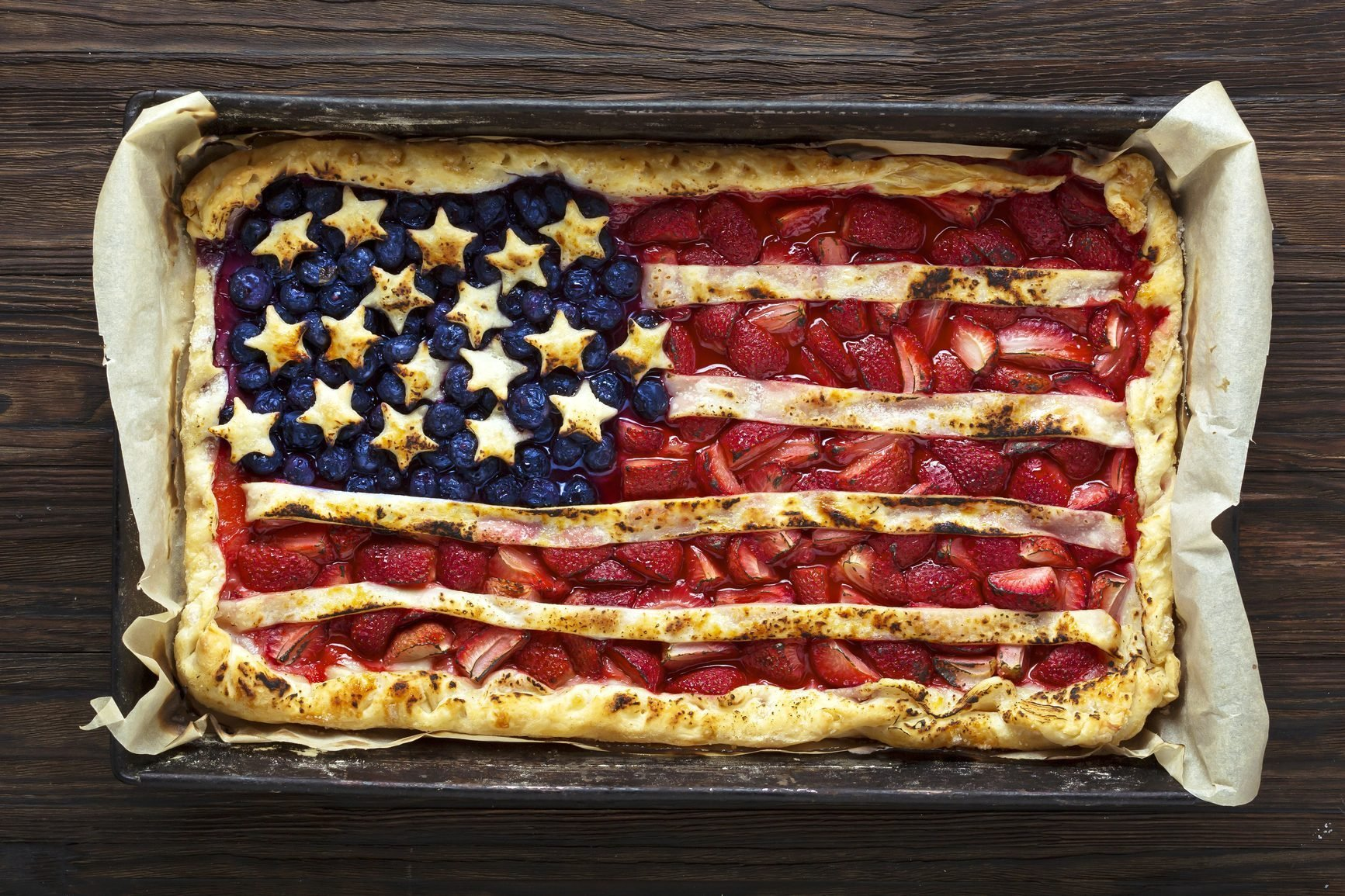 overhead view of a fruit tart designed like the american flag in a rectangular pan on a dark wood countertop