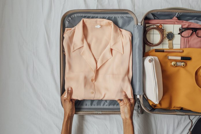 A Woman Packing her Clothes in a Suitcase