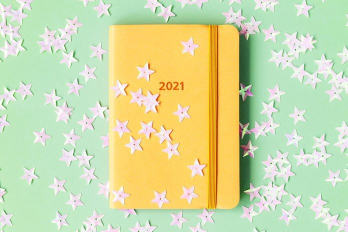 yellow 2021 planner on green background with star confetti