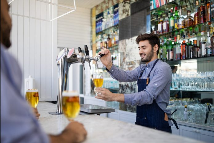Bartender filing beer in a glass from tap