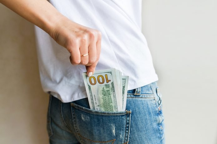 woman got cash money. Richness and wellbeing concept. Get cash money easy and quickly. one hundred dollar bills is in back pocket of jeans. Financial banking, shopping, business concept