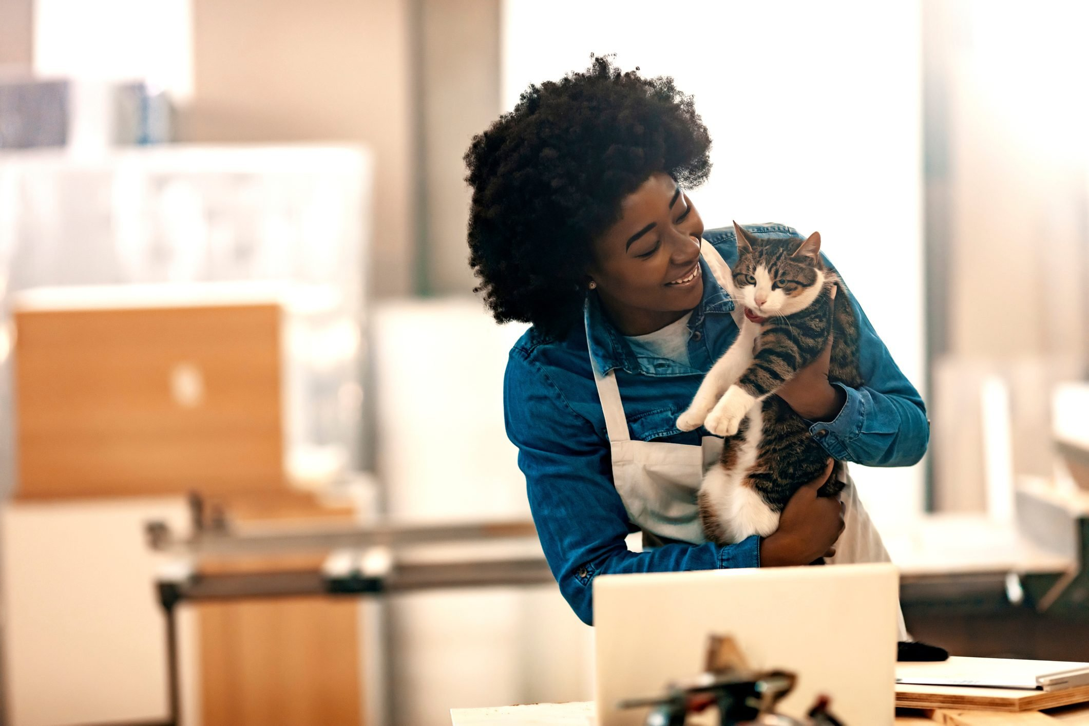 Smiling young woman with cat in workshop