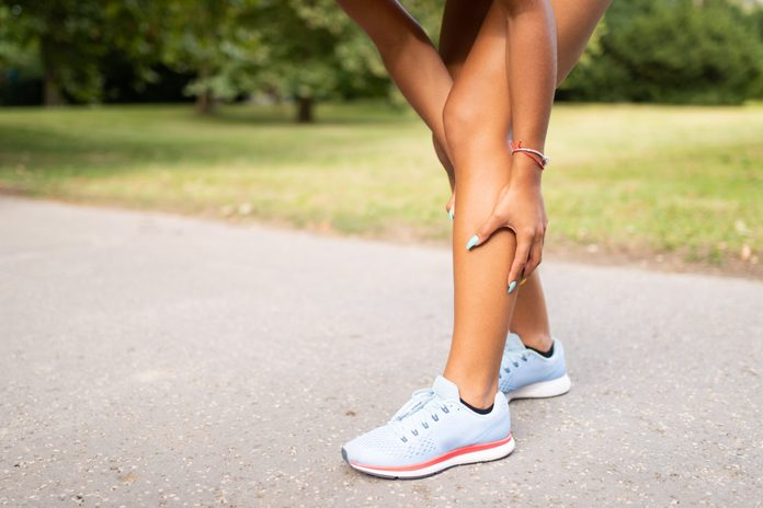 Woman holding her leg due to muscle tear in calf