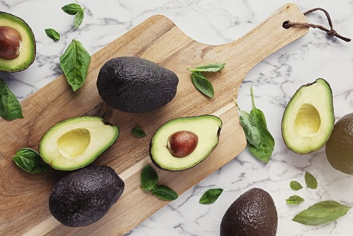 Wooden cutting board with avocados and basil on marble stone