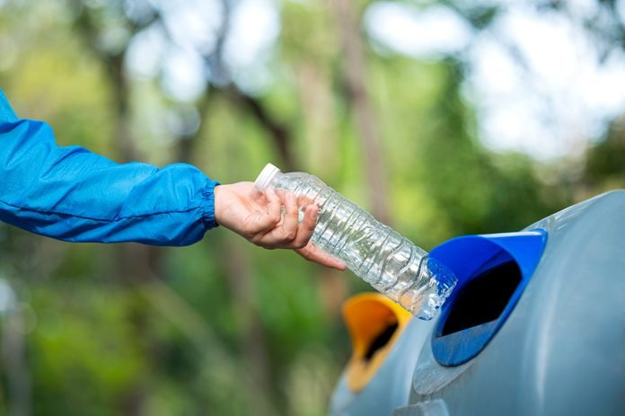 Close-up of woman hand throwing empty water bottle in litter bin outdoors after finishing jogging.
