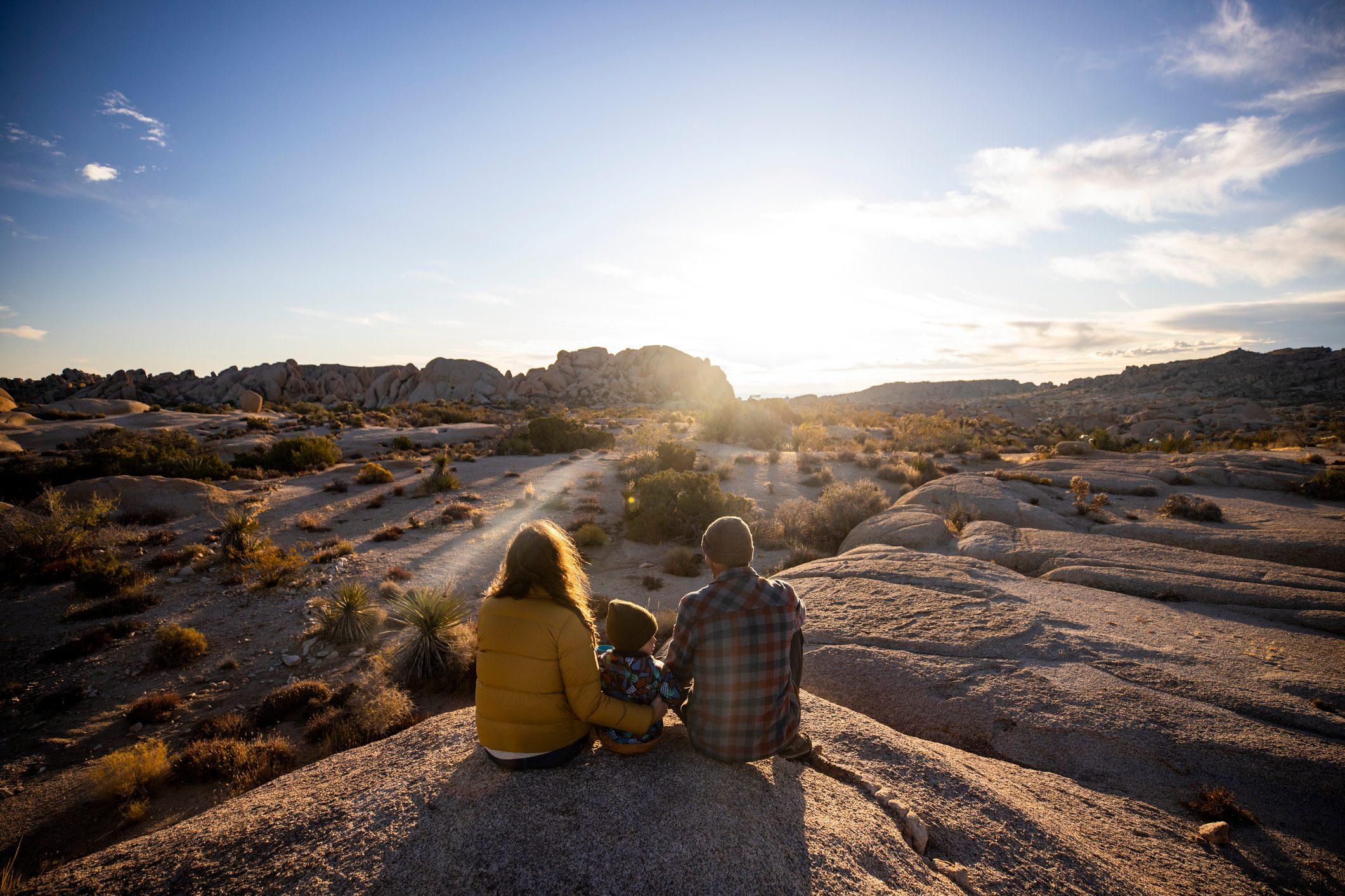 A family sitting on a rock taking in a sunset over the desert.