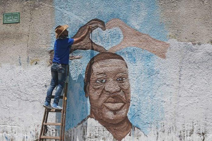 Palestinian artist Ayman al-Housari paints a mural depicting George Floyd in Gaza City on June 16, 2020.