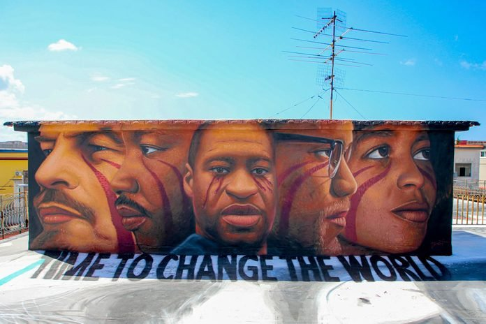 """A mural painting on a roof made by street artist Jorit Agoch depicting George Floyd, Wladimir Ilic Ulianov Lenin, Malcolm X, Angela Davis, Martin Luther King and a write """"Time to change the world""""."""