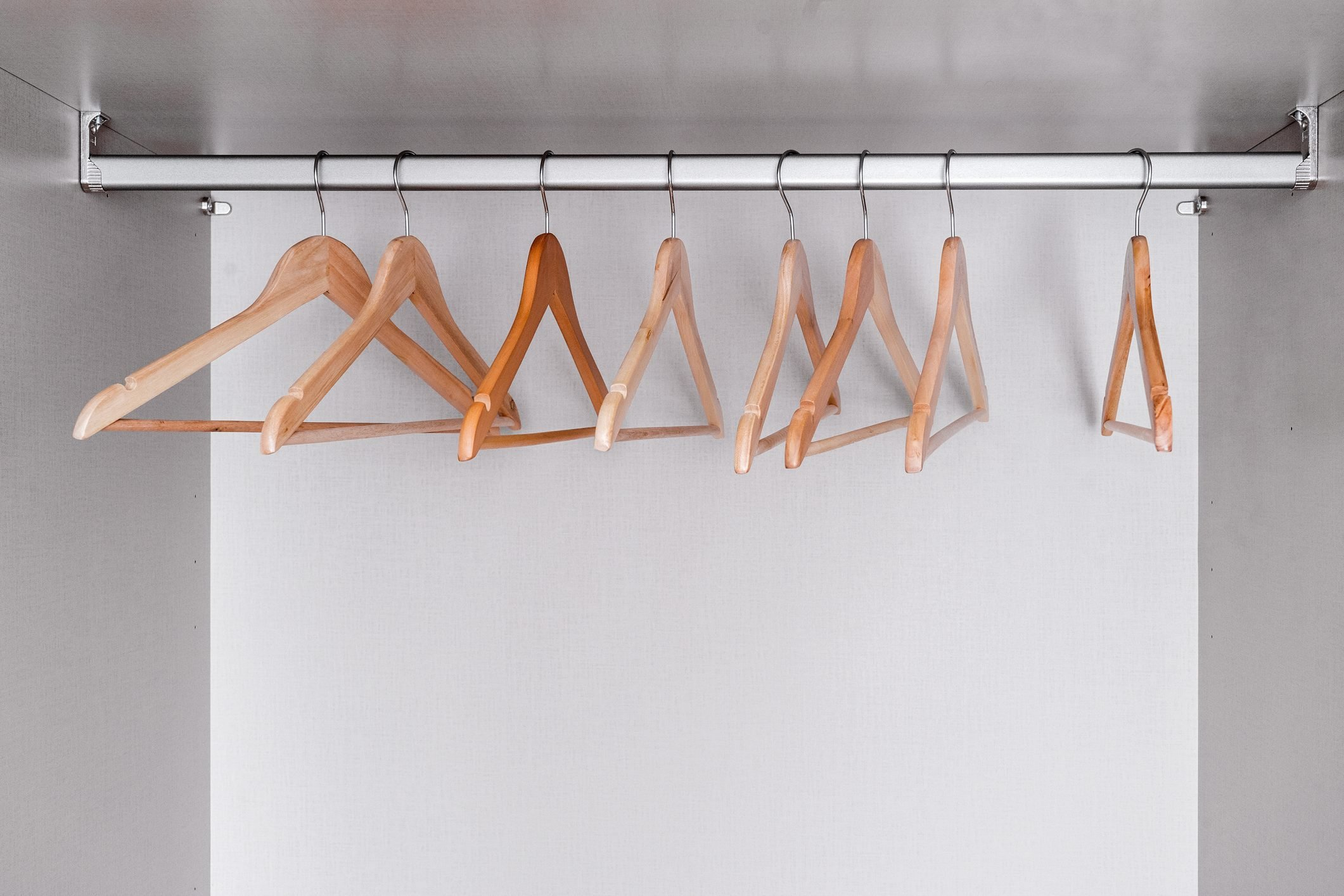 Many empty, lacquered light wood clothes hangers hang in wardrobe on metal rod. Internal space of furniture