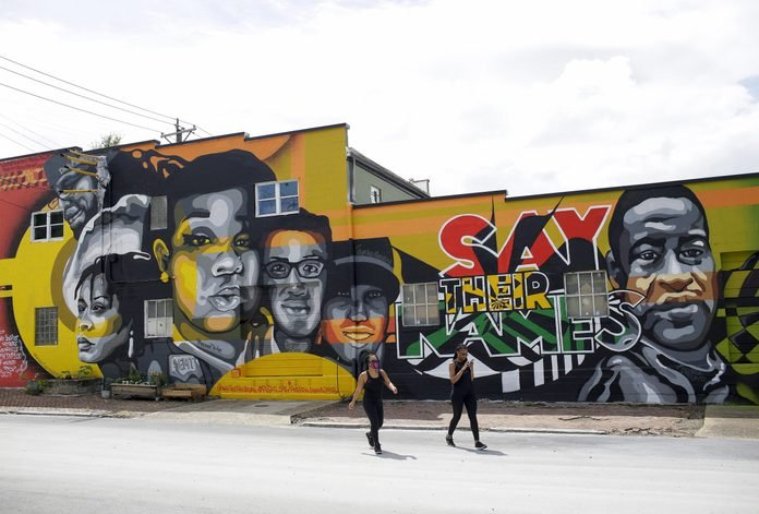 Kimberly King and Genevieve Bell walk away from a mural displaying the face of Breonna Taylor, David McAtee, Sandra Bland, George Floyd and others on a building along 11th Street Saturday, August 1, 2020 in Louisville, Kentucky.