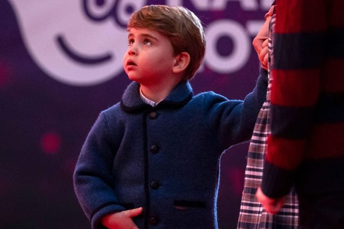 Britain's Prince Louis of Cambridge holds his mother's hand as they attend a special pantomime performance of The National Lotterys Pantoland at London's Palladium Theatre in London on December 11, 2020