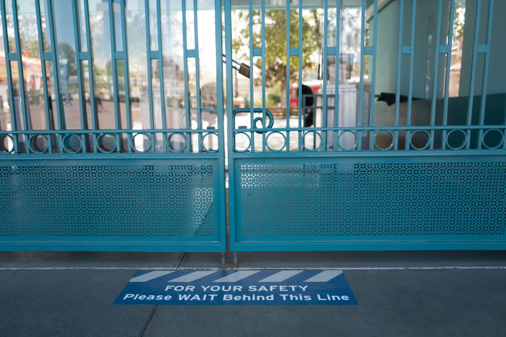 """locked gates at Disney California Adventure Park in Anaheim, CA, with a sticker on the ground that says, """"For Your Safety Please Wait Behind This Line"""""""