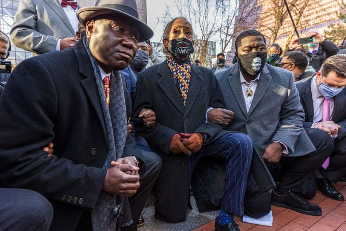 Floyd family lawyer, Attorney Ben Crump (L) and Rev. Al Sharpton, the founder and President of National Action Network,(C) and George Floyd's brother kneel outside the Hennepin County Government Center on the opening day of the trial of former Minneapolis police officer Derek Chauvin on March 29, 2021 in Minneapolis, Minnesota.