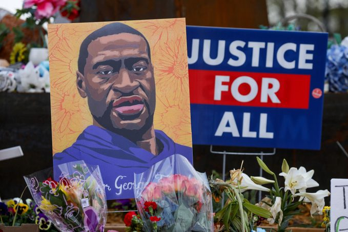 """a portrait of George Floyd, a """"Justice For All"""" sign, and flowers lay at a memorial in George Floyd Square in Minneapolis, Minnesota"""
