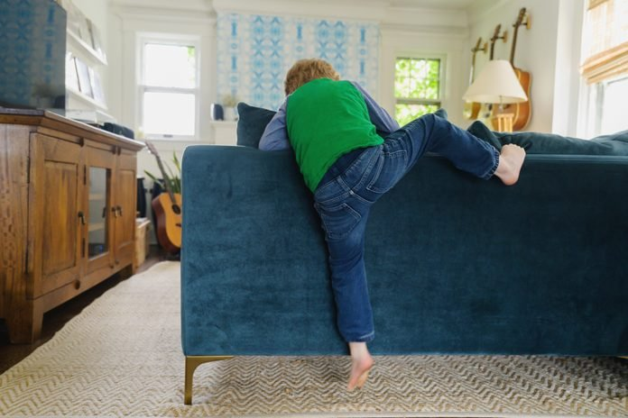 Rear view of boy (4-5) climbing over back of couch