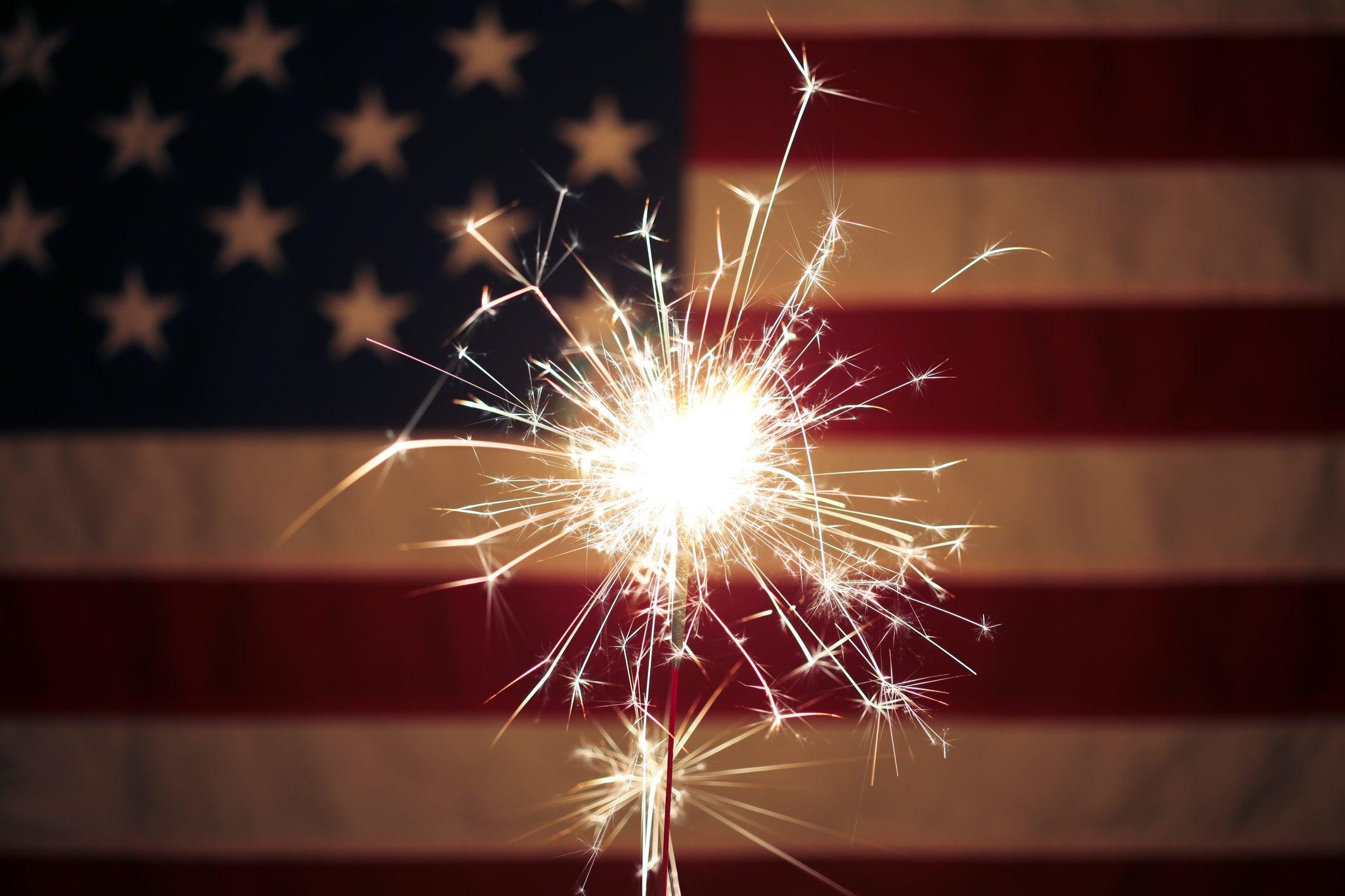 Lit sparkler in front the American Flag for 4th of July celebration