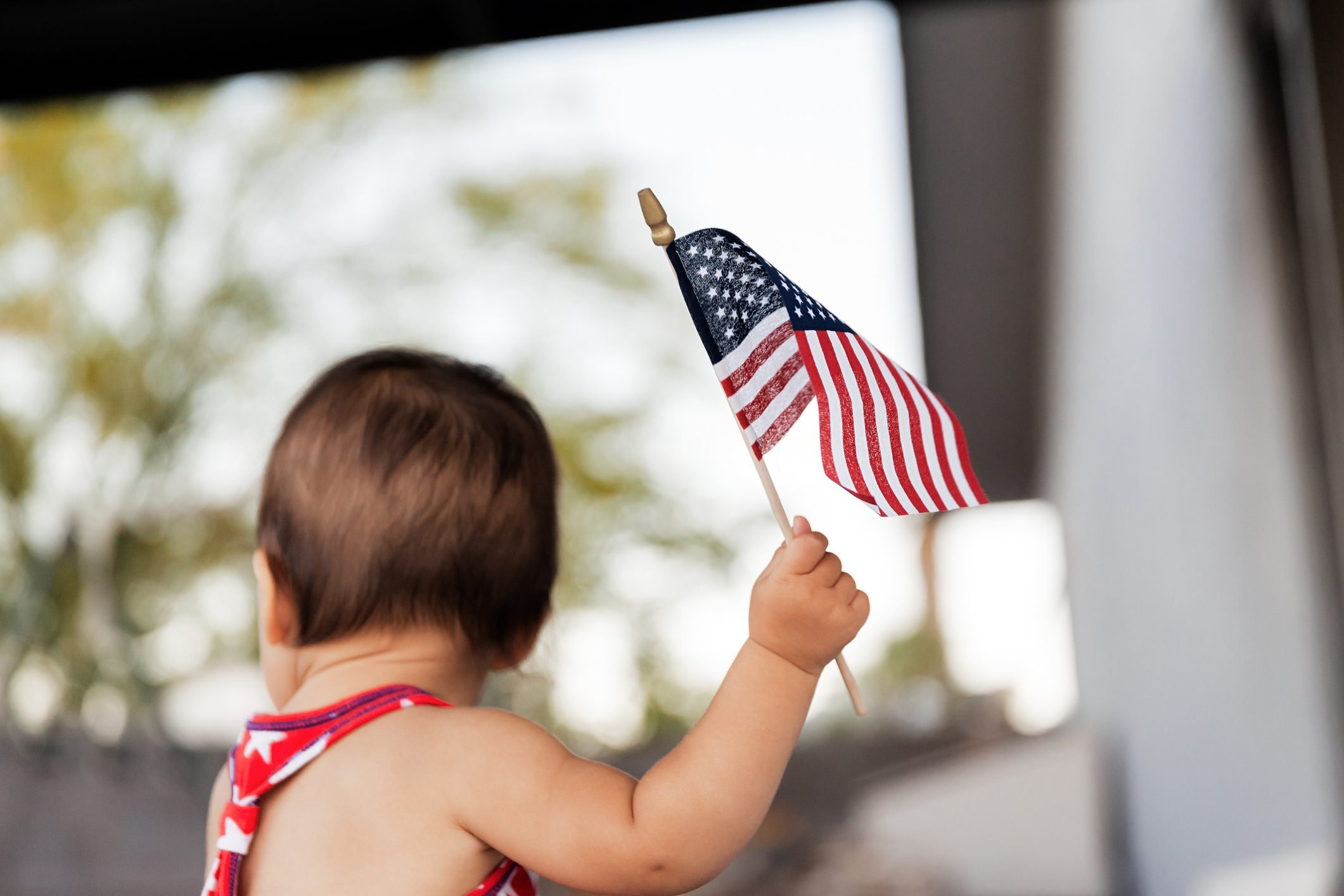 Rear View Of Baby Girl Holding American Flag