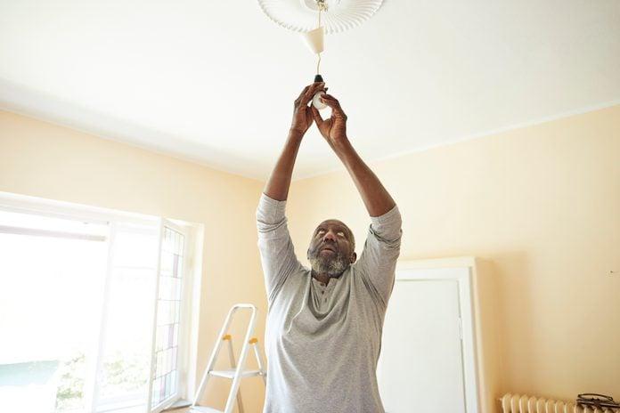 Man changing light bulb while renovating home