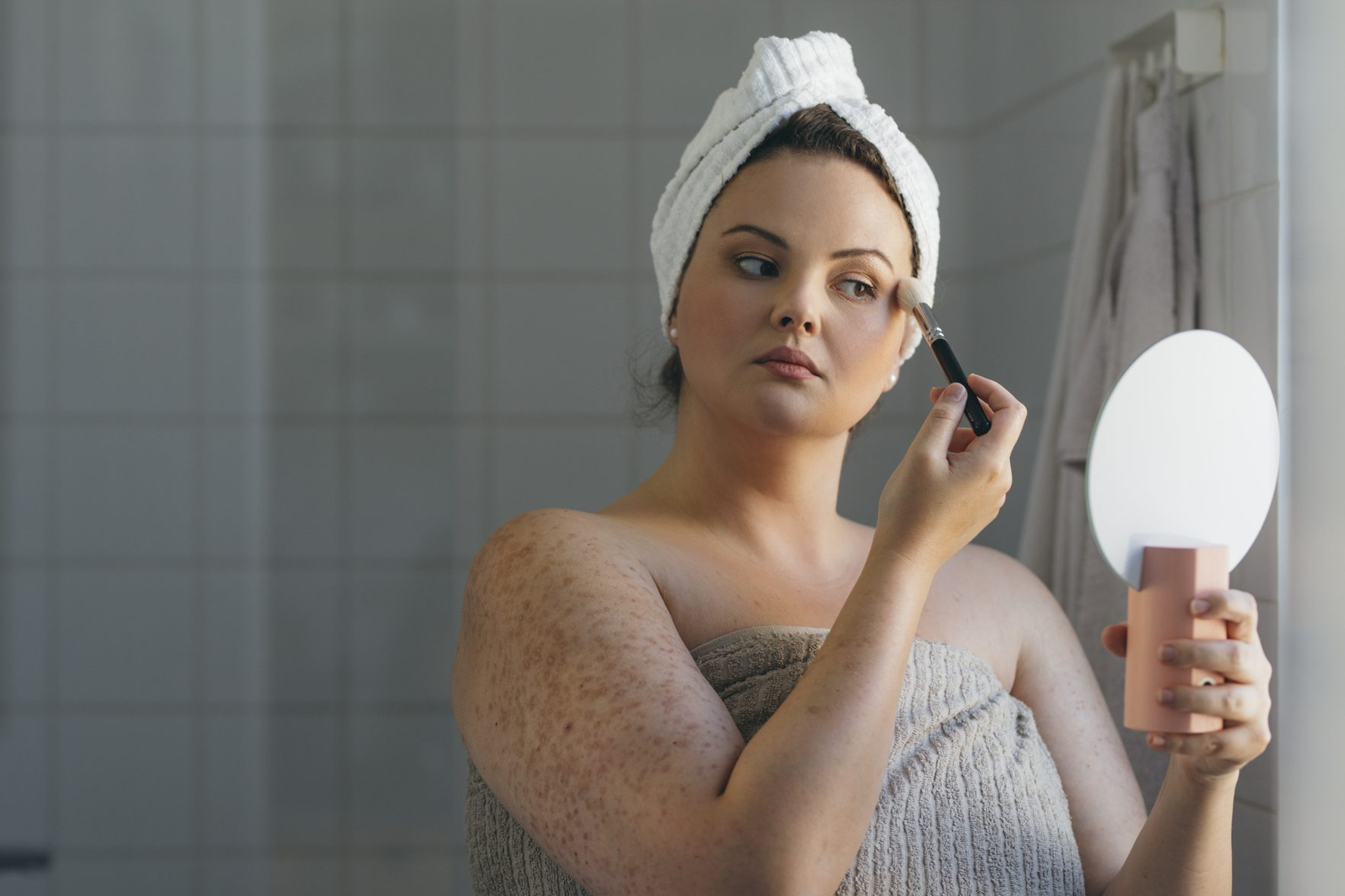 Beautiful Plus Size Woman, Wrapped in a Towel, Applying Makeup onto her Face in the Morning