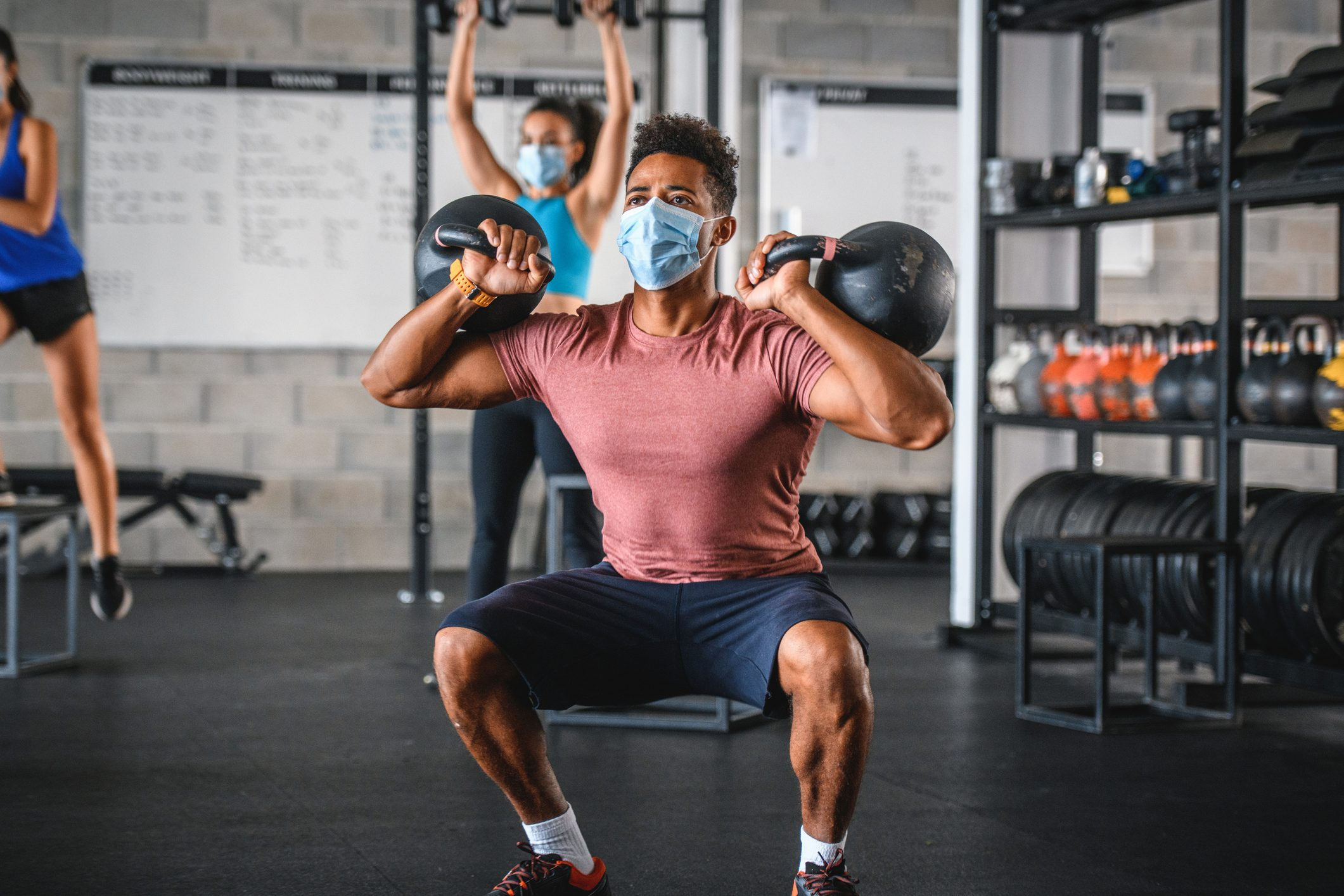 Masked Athlete Doing 2-Kettlebell Front Squat in Gym