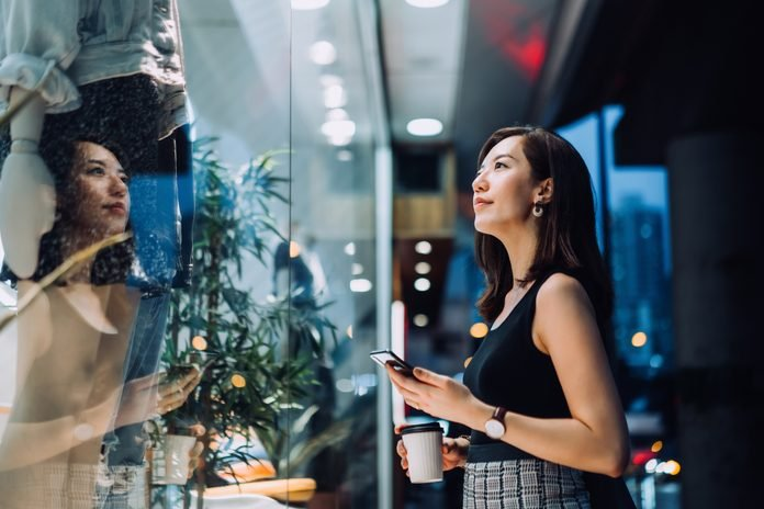 Cheerful young Asian woman holding a cup of coffee, checking her smartphone while standing outside a boutique looking at shop window in the evening in the city