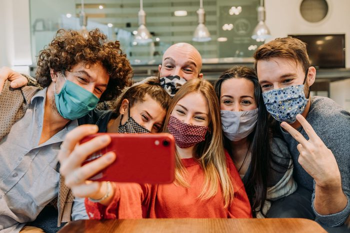 group of friends wearing face masks leaning in together for a selfie in a restaurant