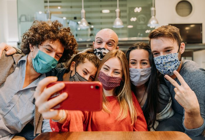 Group of friends wearing protection mask at the restaurant - Young happy people celebrating taking a selfie with smartphone - People, technology and new normal lifestyle concept.