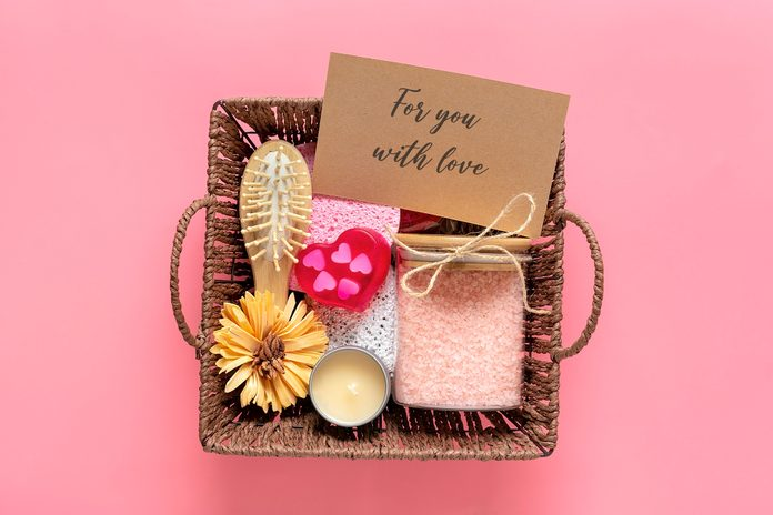 Care box Set of eco-friendly cosmetics Bath salt, wooden comb, pumice stone, aroma candles, handmade soap in shape of heart, sponge for washing on pink background Gift for girlfriend, mother Top view