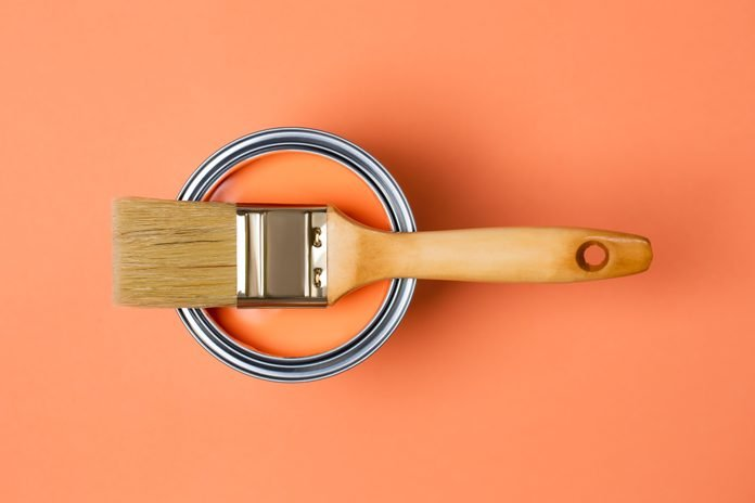 Clean paintbrush on metal bucket with bright orange paint for renovation works on orange coral peach background. Flat lay style. Copy space for your design. Concept of redecoration in home interior. Color swatch for design ideas