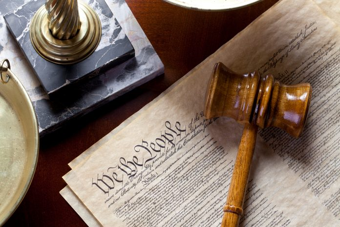 US Constitution with scales of justice and gavel on wood table.