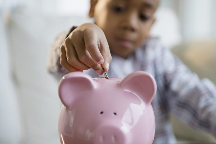 African American boy putting coins in piggy bank