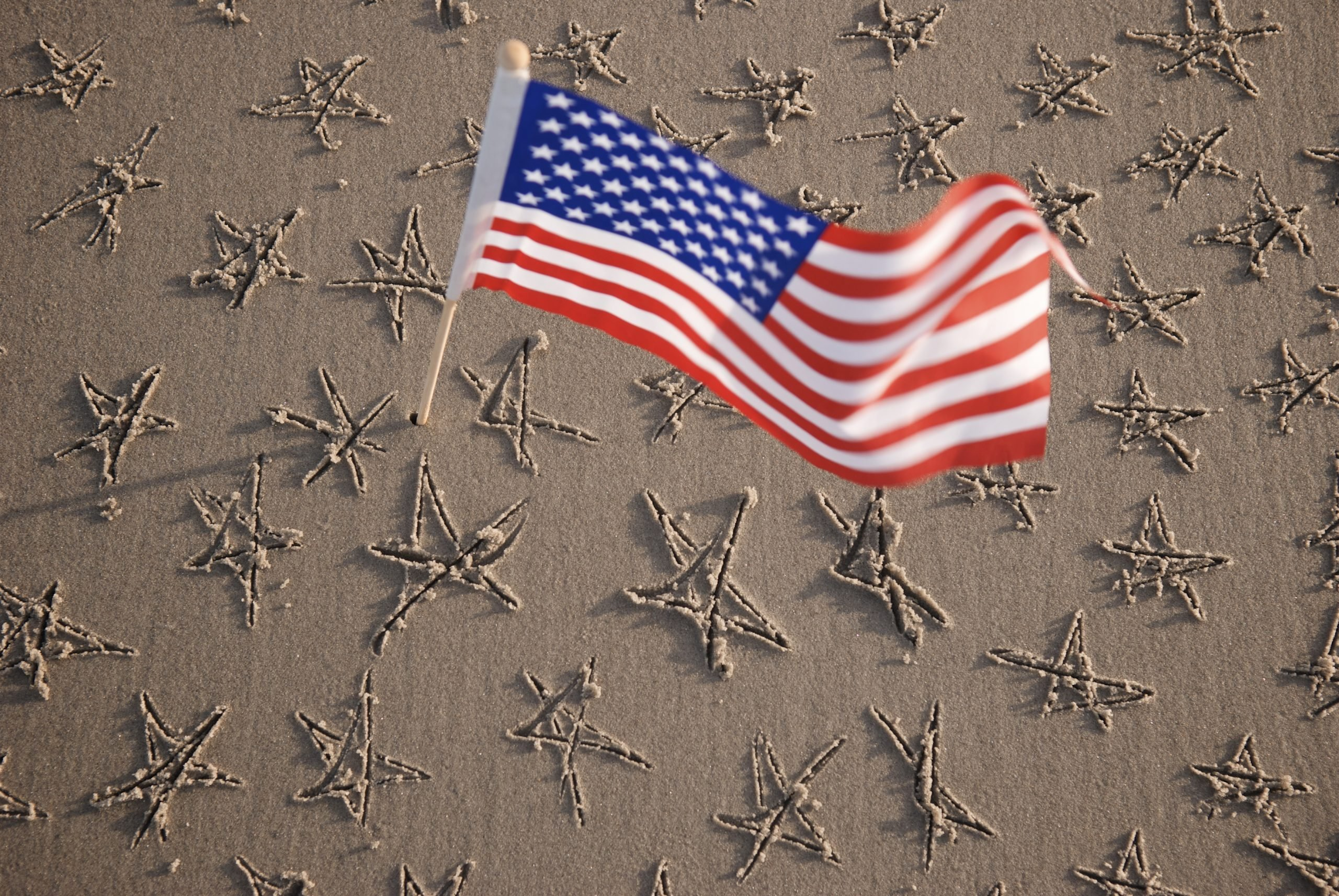 an American flag waves above a stretch of sand with hand-drawn stars