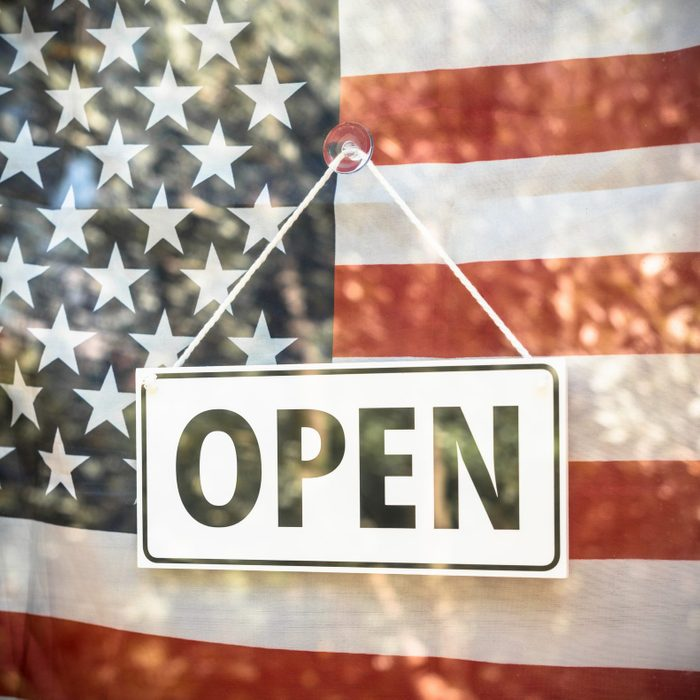 open sign in a store window with american flag behind it
