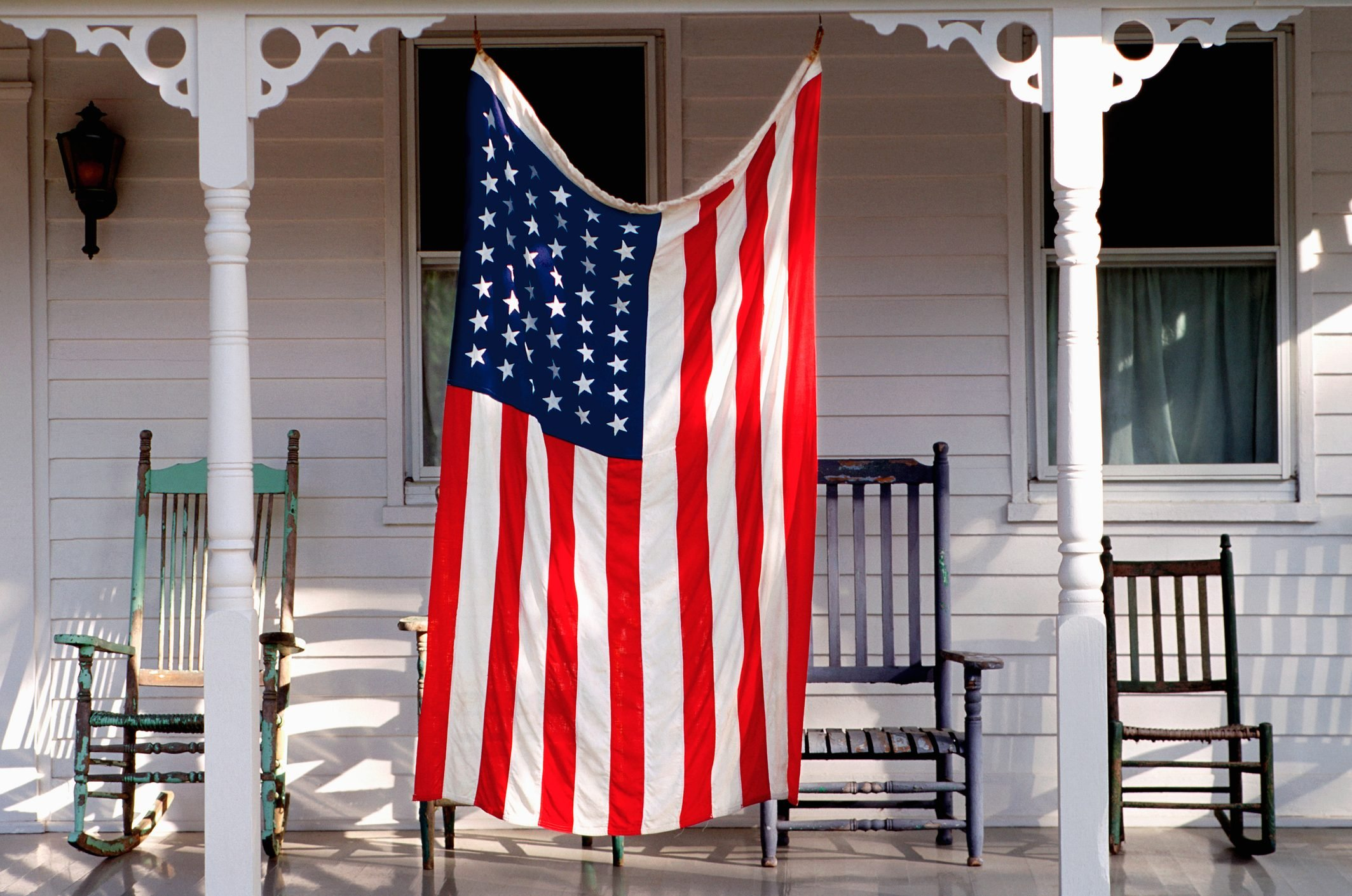 a larg american flag hanging on porch in front of four rocking chairs