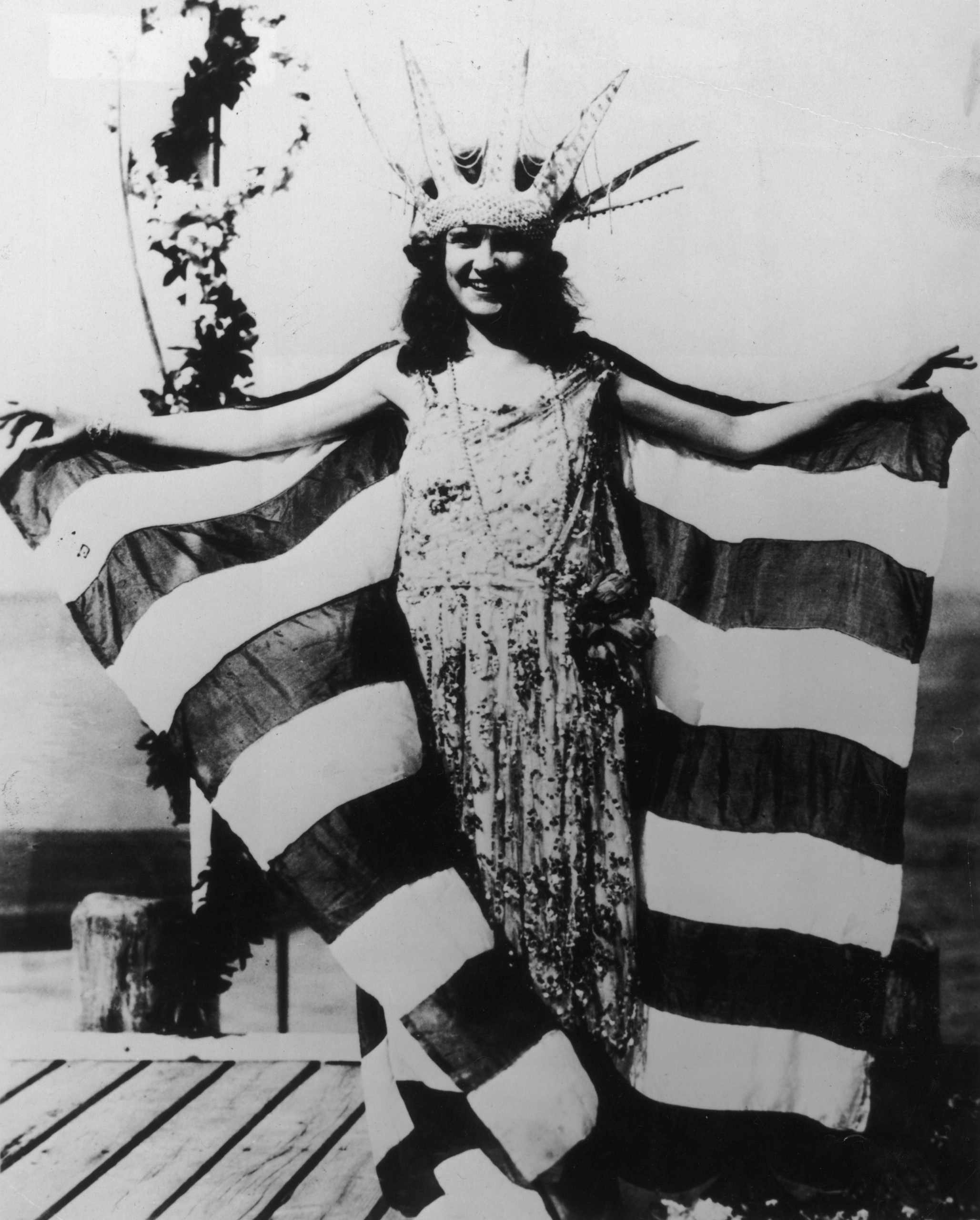First Miss America standing in front of flag