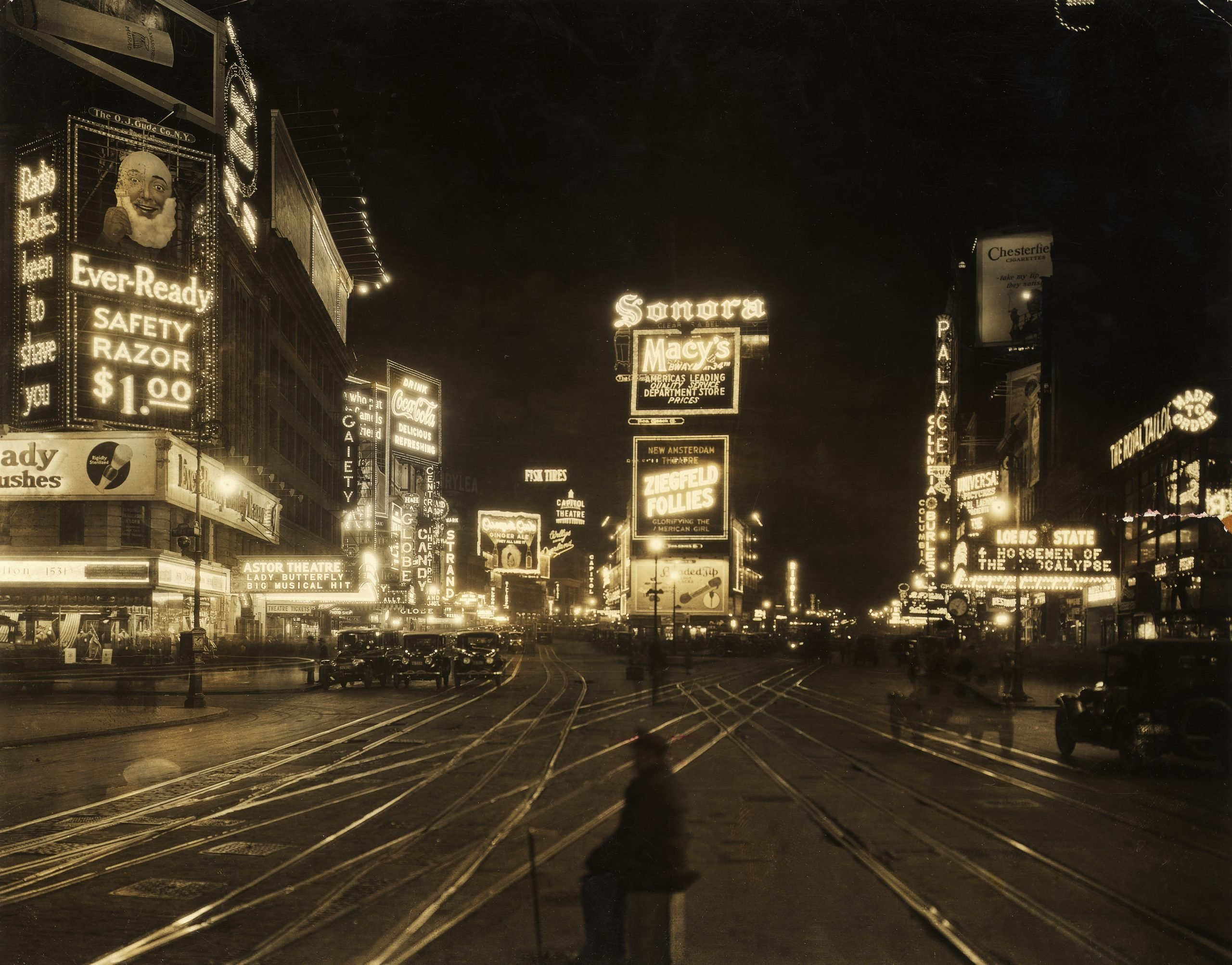 1921: View of the traffic and illuminated advertisements in Times Square at night, seen from 45th Street looking northward, New York City.