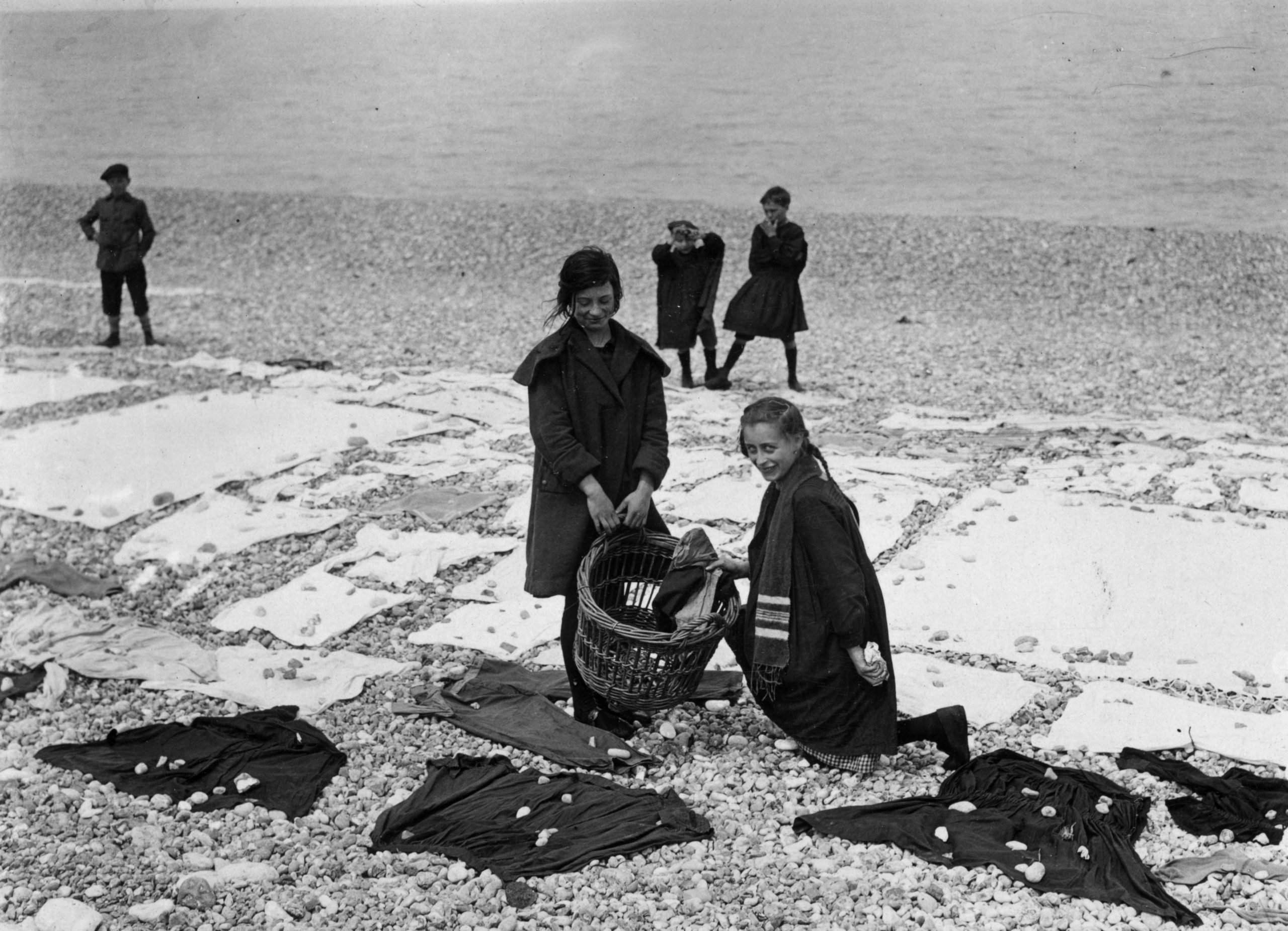 Girls weigh down clothes with pebbles at the beach on washing day
