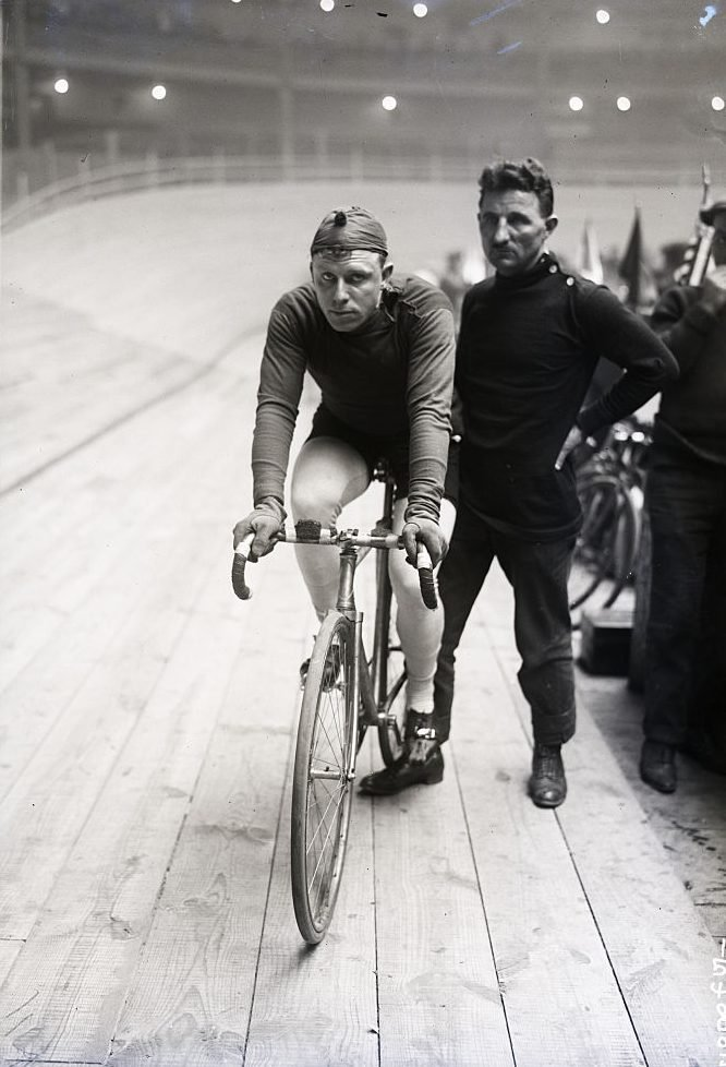 Two Men One On A Bike Other Standing